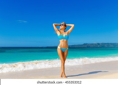 Young beautiful girl in blue bikini having fun on a tropical beach. Blue sea and sky in the background. Summer vacation concept.