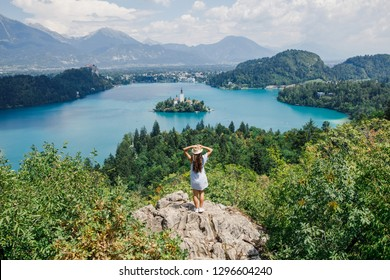 young beautiful girl in a blue dress and hat stands against the backdrop of Lake Bled in Slovenia