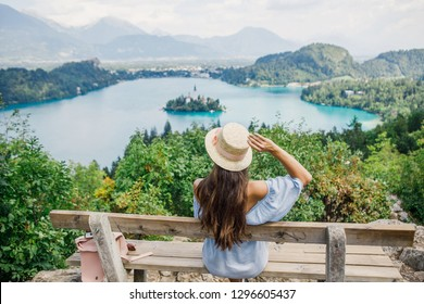 young beautiful girl in a blue dress and a hat sits on a bench on the background of Lake Bled in Slovenia