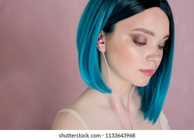Young beautiful girl with blue hair is holding a smartphone, with are pink headphones in her ears. Cropped photo.