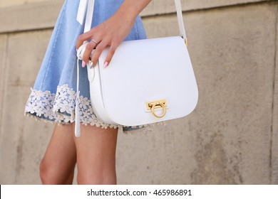 Young beautiful girl in blue jeans skirt with lace and white leather bag in his hand. Stylish snow-white handbag in woman's hands.