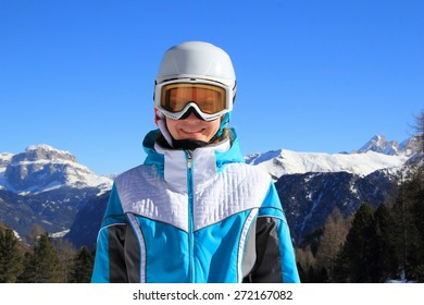 young beautiful girl in a blue ski suit and a white helmet on his head on a background of mountains