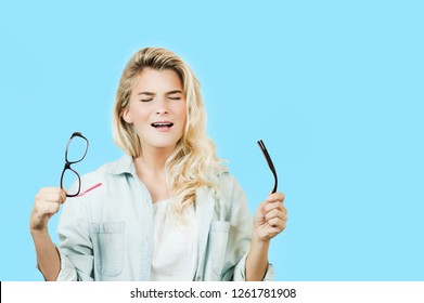 Young beautiful girl with broken glasses and lenses in hands on a blue isolated background. Concept of vision, health