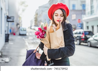 Young beautiful girl brunette in red beret and black coat goes along the street of the European city with bouquet of flowers and French baguettes. happy smile and charming look, French style of Paris