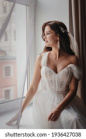 A Young beautiful girl a brunette in a white wedding dress. Morning of the brite at the hotel