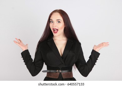 Young beautiful girl in business suit  rejoices, spread her hands to the sides. On a white background. Emotions.