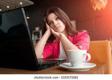 Young, beautiful girl, businesswoman, sitting in cafe and working on laptop. business lunch, cup of coffee, successful business woman.