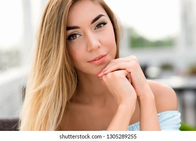Young and beautiful girl in the cafe with long hair. Closeup woman portrait. Tanned skin and casual makeup. Emotionally tender smile and insightful look.