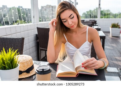 Young and beautiful girl in cafe. On table is a cup of coffee or tea. A woman reads a book at dinner in a restaurant. In summer in a cafe on sunny veranda. Paper book leafing through pages.