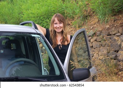 Young beautiful girl in the car on the nature