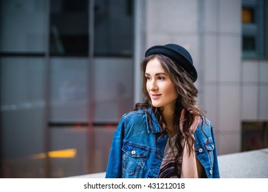Young beautiful girl in casual clothes on a background of the business center, coffee shop. Girl dressed in a denim jacket and a black bowler.