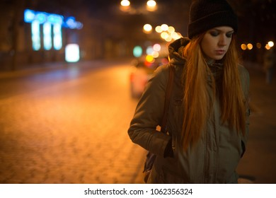 Young beautiful girl catches a taxi in the city street at night