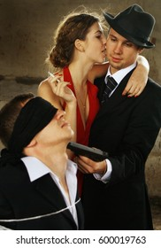 Young beautiful girl with a cigarette in a red dress, a man in a black suit with a gun