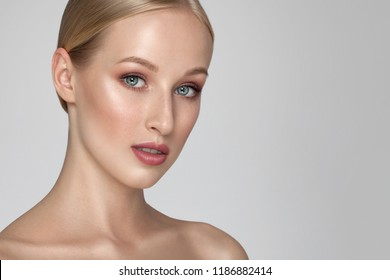 Young beautiful girl with clean healthy face skin, salon skin care concept. Portrait of Beauty woman on grey background