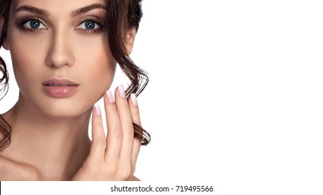 Young beautiful girl with clean skin and white nails, isolated on white background. Beauty brunette woman with French manicure, keep the streak of hair on his finger. Grey eyes