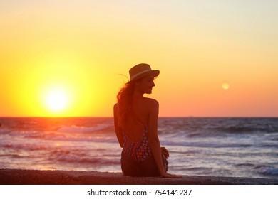 Young beautiful girl closeup near the sea at the sunset.