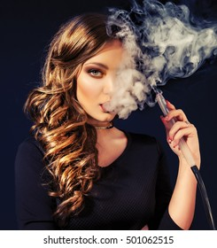 Young, beautiful girl in club dress and perfect make up smoke a hookah. The pleasure of smoking. Sexy smoke