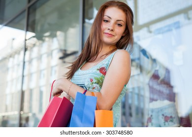 Young beautiful girl with colorful shopping bags. Season of sales