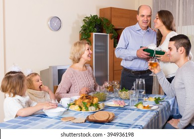 Young beautiful girl congratulating heartily family member at the table at home