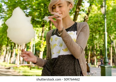 Young beautiful girl with cotton candy in the park