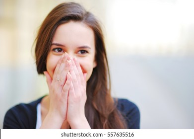young beautiful girl covering her mouth with his hands for joy
