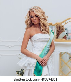 Young beautiful girl with crown and ribbon in interior luxury castle. Beauty Queen