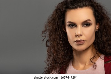 Young beautiful girl with curls on her head with a serious facial expression on a gray background. Portrait of a woman with a strong face with brown eyes in a pink T-shirt and red suspenders