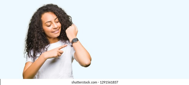 Young beautiful girl with curly hair wearing casual white t-shirt In hurry pointing to watch time, impatience, upset and angry for deadline delay