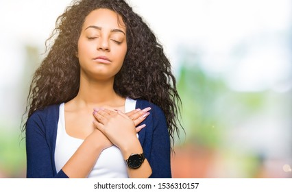 Young beautiful girl with curly hair smiling with hands on chest with closed eyes and grateful gesture on face. Health concept.
