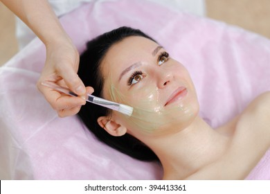 Young beautiful girl with dark hair gets procedure with collagen mask in a beauty salon. Face Skin Care. Cleansing Procedure. Cosmetology.