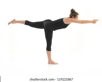 young, beautiful girl demonstrating difficult yoga posture, dressed in black, on whie background