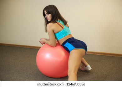 Young beautiful girl does exercises with a fitball in a fitness center.