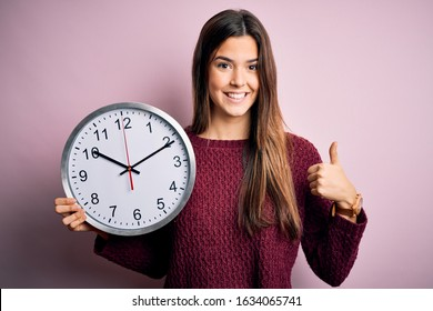 Young beautiful girl doing countdown holding big clock over isolated pink background happy with big smile doing ok sign, thumb up with fingers, excellent sign