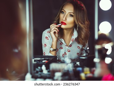 Young beautiful girl doing makeup with red lipstick