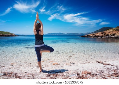 Young Beautiful girl doing yoga at the beach on a sunny calm day. Girl relaxing with yoga activity