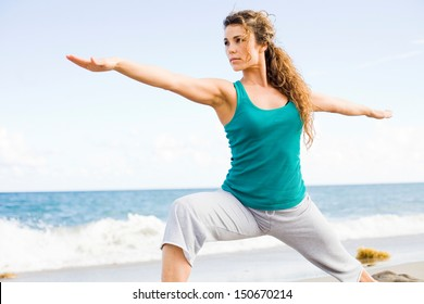 young beautiful girl doing yoga on the beach in warrior pose.