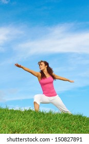 young beautiful girl doing yoga in warrior pose on a beautiful day with clear blue sky.
