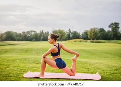 Young beautiful girl doing yoga outdoors