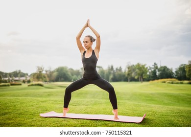 Young beautiful girl doing yoga outdoors
