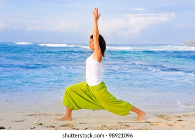 Young beautiful  girl doing yoga on the beach