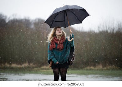 Young beautiful girl with dreadlocks in the rain with an umbrella