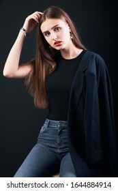 Young beautiful girl dressed in a black jacket and jeans posing in studio. Office modern style. Young elegant business woman.