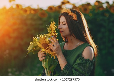 young and beautiful girl dressed in national Ukrainian costumes standing near sunflowers in the field