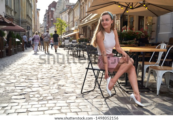 Young beautiful girl dressed in retro vintage style enjoying the summertime lifestyle of old european city