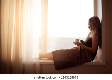 Young beautiful Girl drinking coffee sitting near the window in morning. Blond sexy naked female Boudoir photo standing in front of large window wrapped in blanket with her back to camera