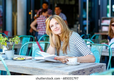 Young beautiful girl drinking coffee and reading book in an outdoor cafe in Europe. young woman enjoying summer in Paris, France