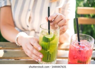 Young beautiful girl drinking cold drink beverage cocktail outdoors in cafe wooden table. Summer lifestyle people.