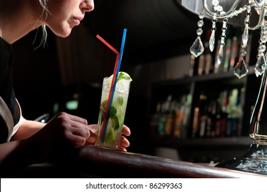 A young beautiful girl drinking cool mohito with a straw in a cafe