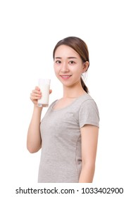Young beautiful girl is drinking a glass of milk