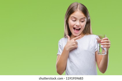 Young beautiful girl drinking glass of water over isolated background very happy pointing with hand and finger